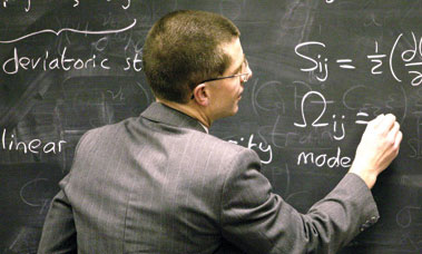 Member of staff writing on a blackboard